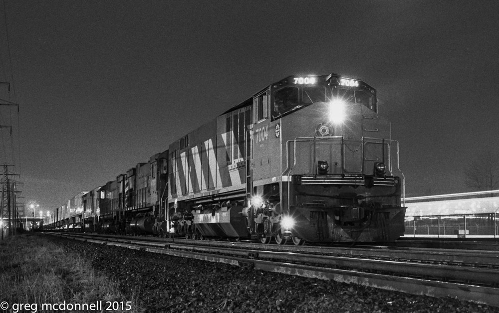 With borrowed Bombardier HR616 demonstrators 7004 and 7001 bracketing M636 4703 and M630 4511, CP's Toronto-Montreal intermodal train 928 prepares to depart Obico at 23:10, December 12, 1983.