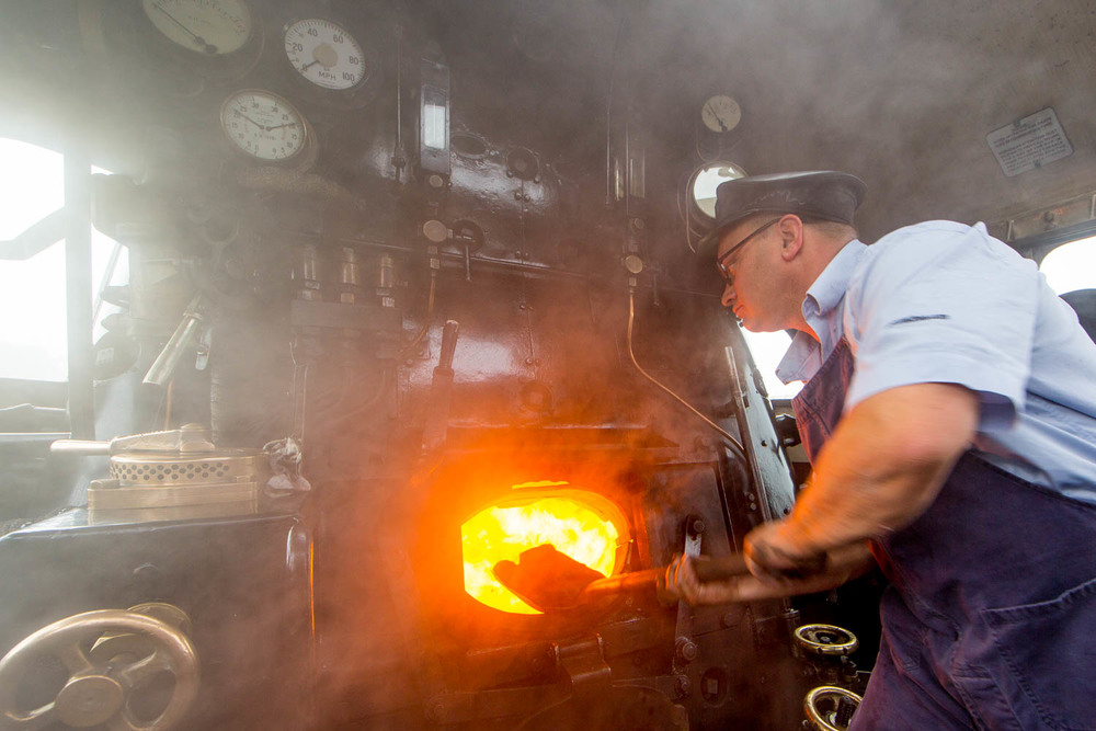 On the footplate (2) Fireman Peter Skinner at work aboard BR Standard 9F 2-10-0 No. 92214 on the 10:00 Great Central train from Loughborough Central to Leicester North. 27 September, 2015