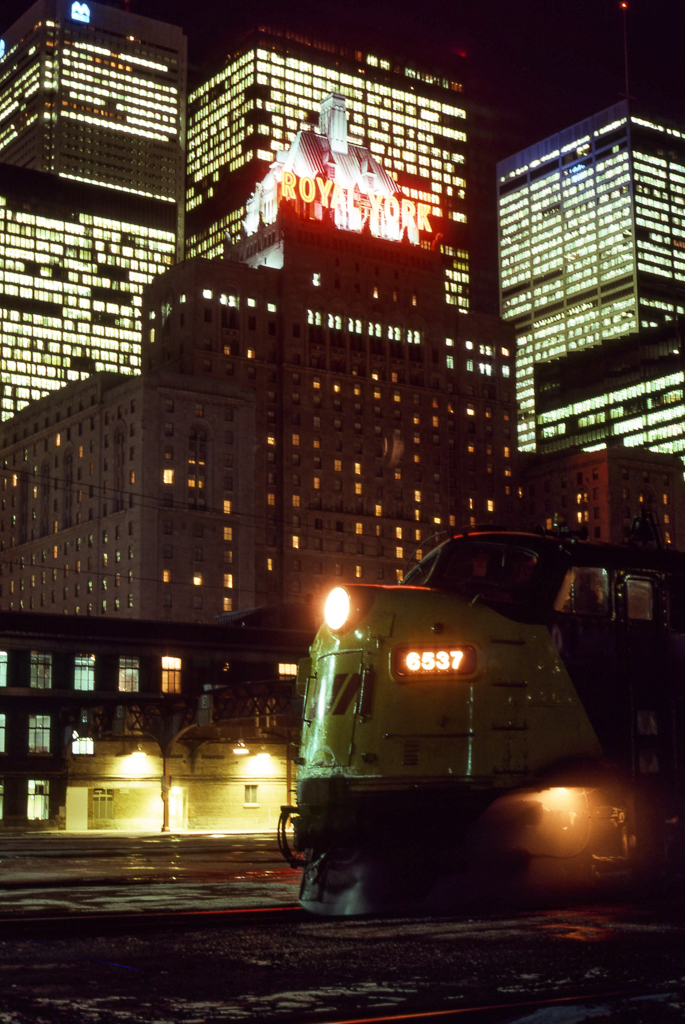 City lights. Waiting to depart Union with Toronto-Windsor train 79, VIA FP9 6537 basks in the warm neon glow of the Royal York Hotel. December 17, 1979.