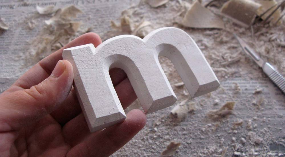 A hand carved plasterboard letter.