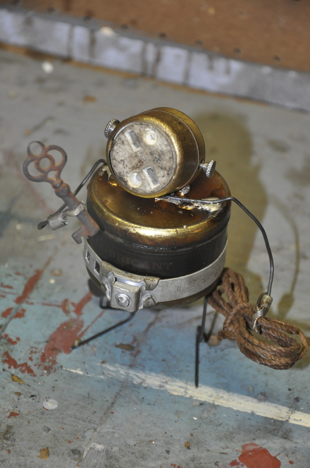 """""""The Tinkerer""""    Part of the series; """"God's Golden Garbage.""""    Electrical socket, key, steel wire, misc. hardware. 2011"""