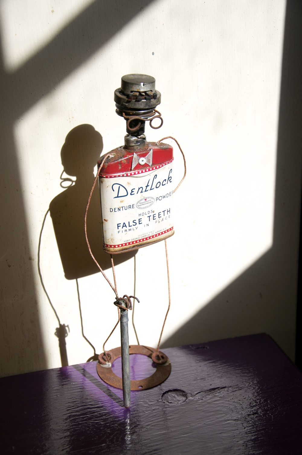 """""""Norm's Big Day Out""""    Part of the series; """"God's Golden Garbage.""""    Denture powder can, steel wire, misc. hardware, projector parts. 2012"""