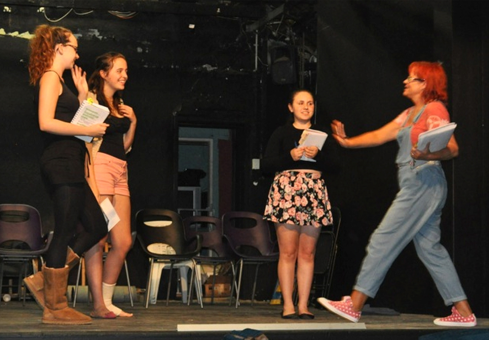Teens busy themselves on the Garrick Theatre stage.