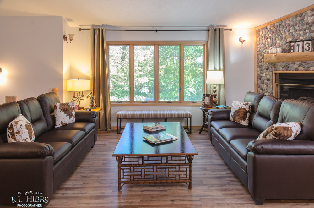 WELCOMING GREAT ROOM OFFERS BEAUTIFUL VIEWS OF THE MEADOW LAKE GOLF COURSE THROUGH THE TREES.