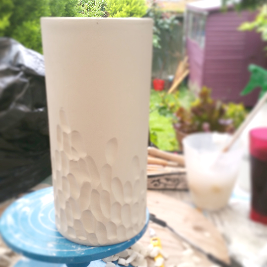 Clara Castner carving large porcelain vase in garden.jpg