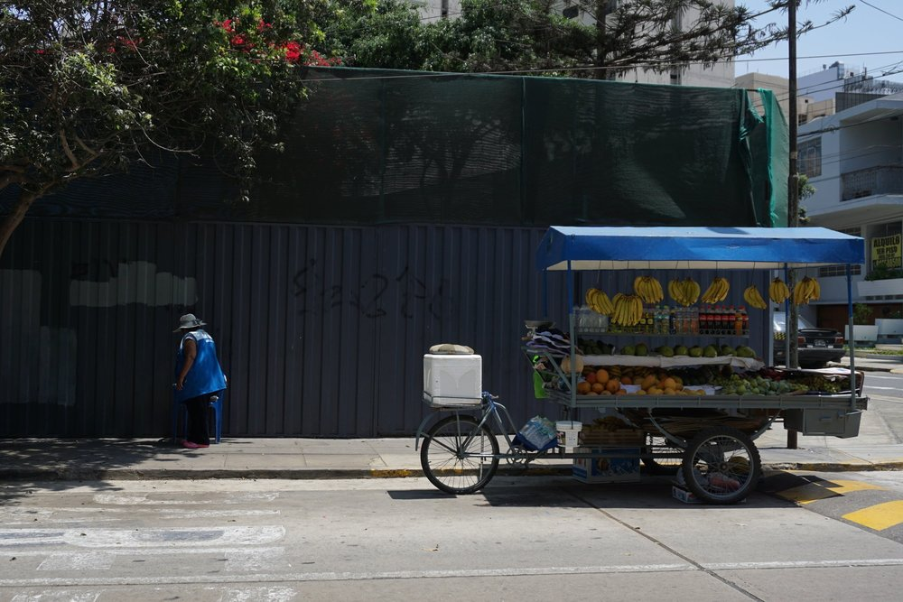 A fruit vendor finding a shaded spot to sit on a hot day in Lima's Miraflores district.
