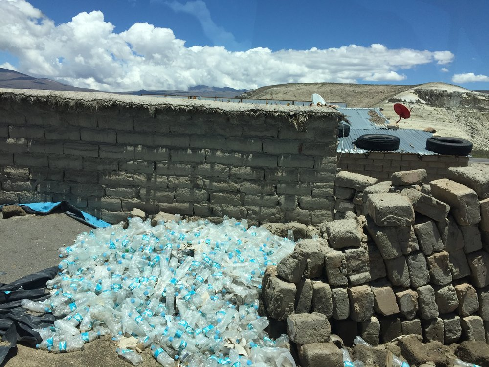 Municipal water supplies are not to be trusted in Peru; bottled water is the way to go to prevent illness. Unfortunately, all that waste has to end up somewhere (here in the back of house in the altiplano, miles from anywhere).