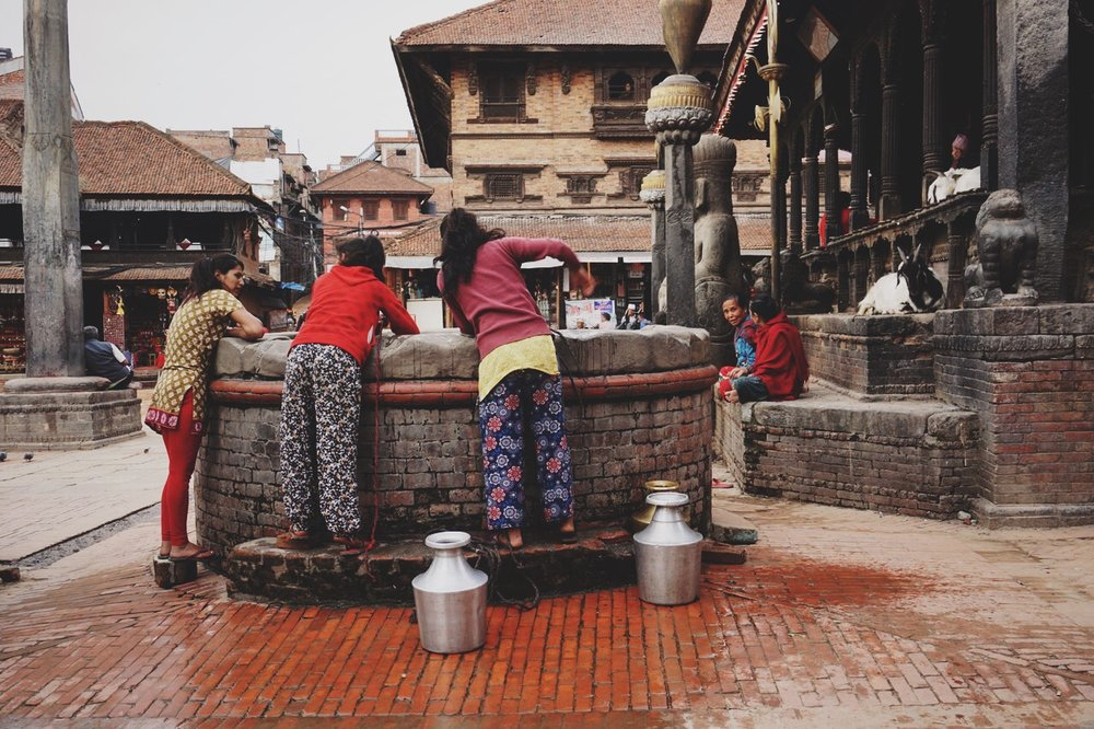 Nepali girls getting water out of a well in Durbar Square