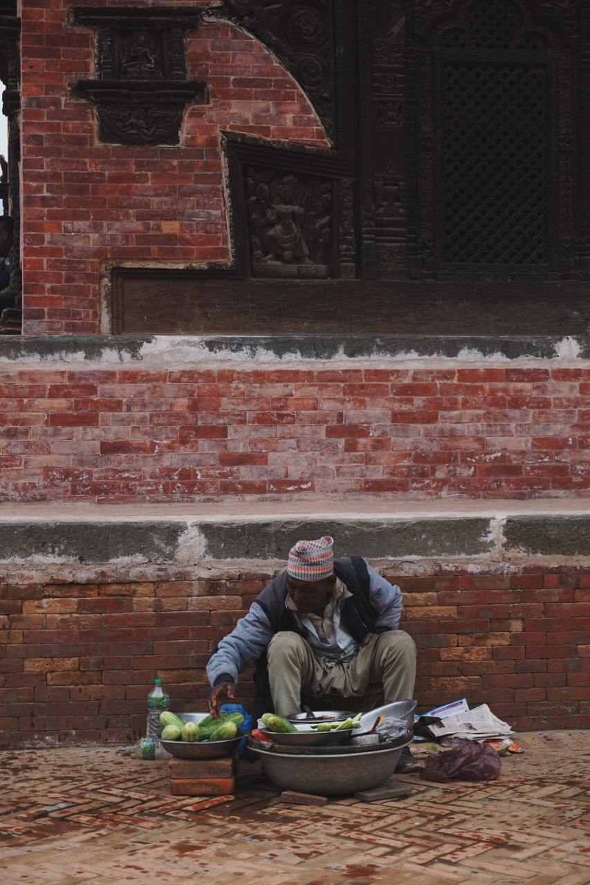 A vendor in front of one of Bhaktapur's traditional buildings decorated with complex woodwork