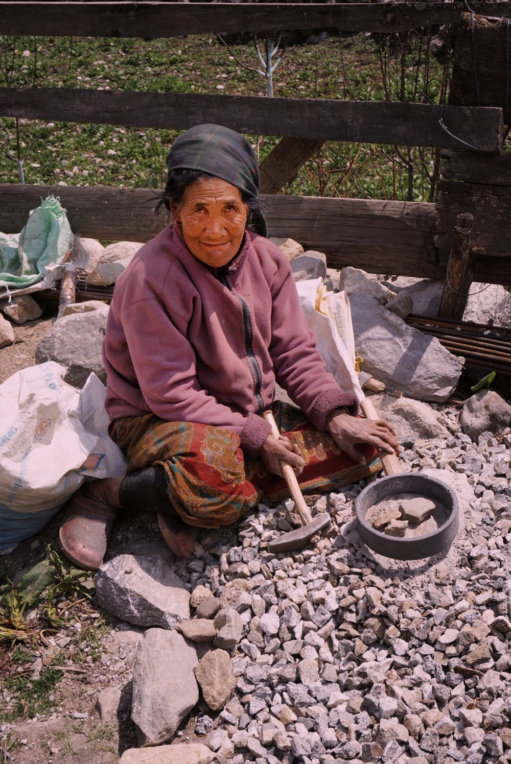 Elder woman in the village of Thanchowk breaking stones into smaller gravel for the village path