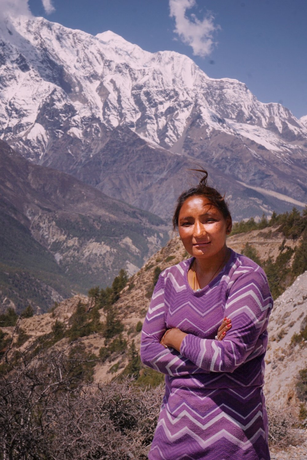 This is Chunda. Each day she packs a bag of drinks and snacks, hikes up to 12,500 ft, and sets up her shop-in-a-bag along the trail, opposite views of Annapurna II and IV.