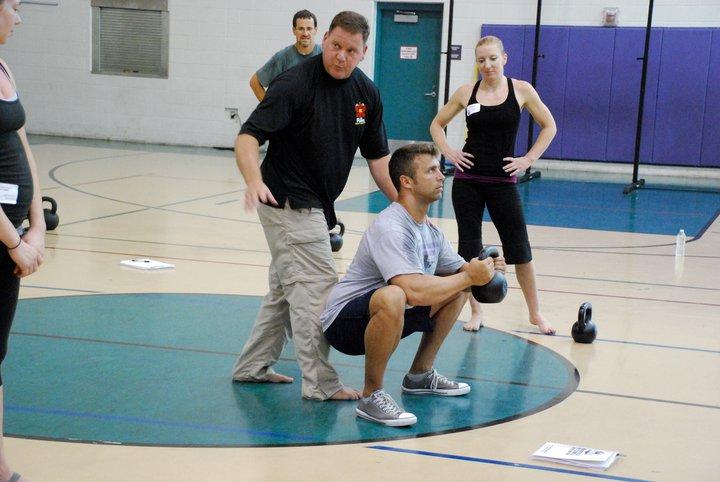 Dan John going over the goblet squat during a kettlebell cert. Source: http://darrenschlechter.com/photos/