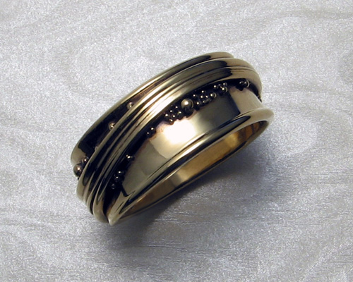 Free-form, wrap-around wedding ring with spherical granulation.