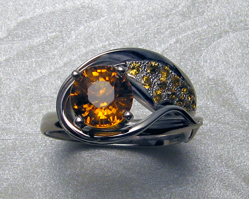 Asymmetrical engagement ring with orange sapphires.