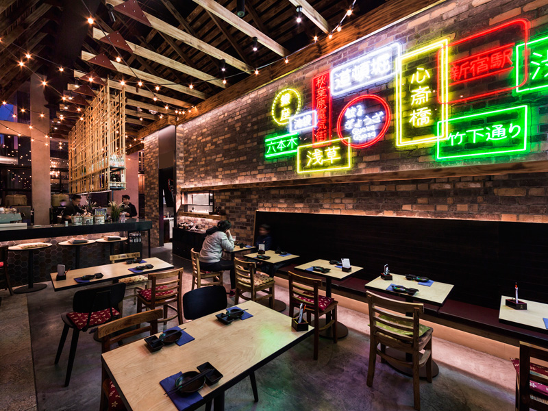Gyoza Gyoza Doncaster. Dark, moody and textured interior with contrasting neon lit wall.