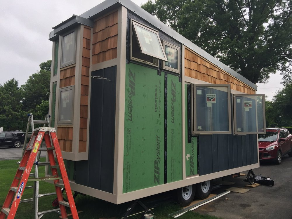 The cedar shakes are coming along, looking great over the blue gray stained board and batten siding on the lower half of the house. The darker gray metal sections will be added soon under the loft windows on both sides.