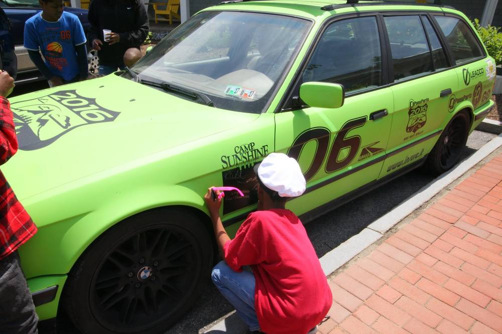 A camper from Camp Sunshine signing the car.