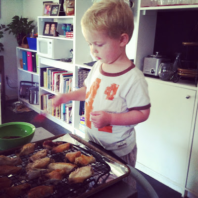 Saucing the wings with the best sous chef EVER.