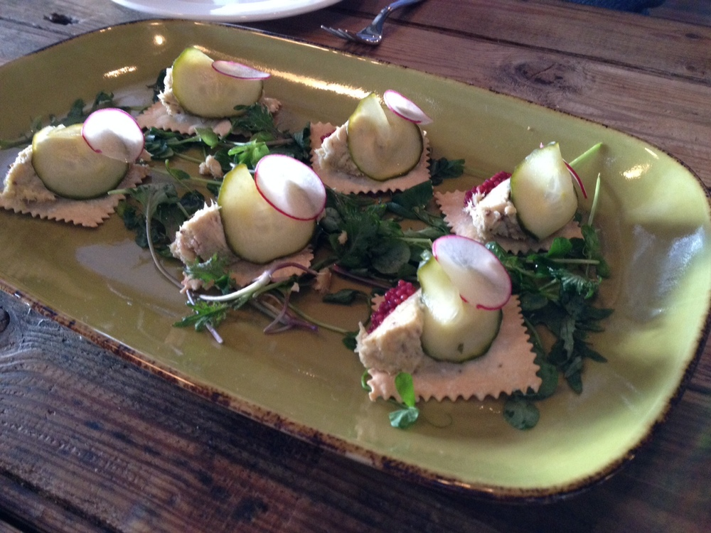 Sturgeon rillettes on house made crackers, with pickles on a bed of pea shoots