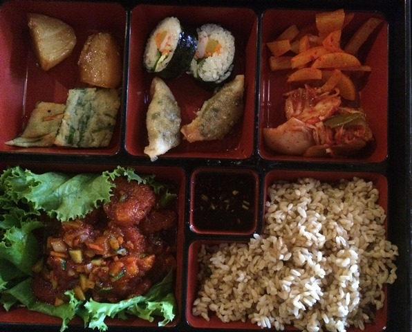 My lunch box with shrimp in a garlic sauce, rice and chef selected sides.