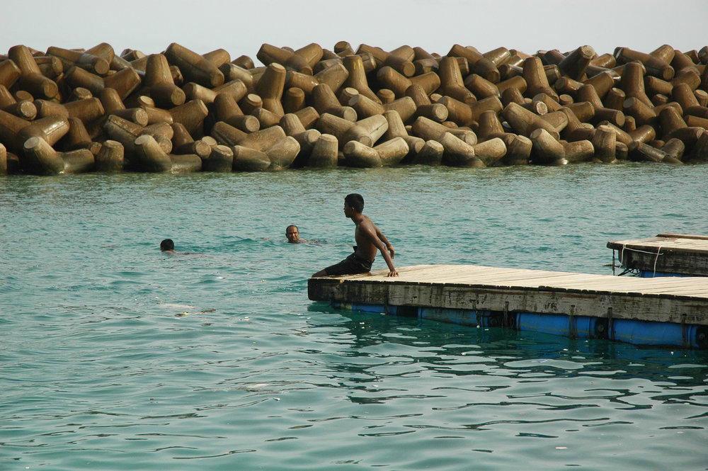 Boy sits at the edge of one of the older iterations of the swimming platforms.