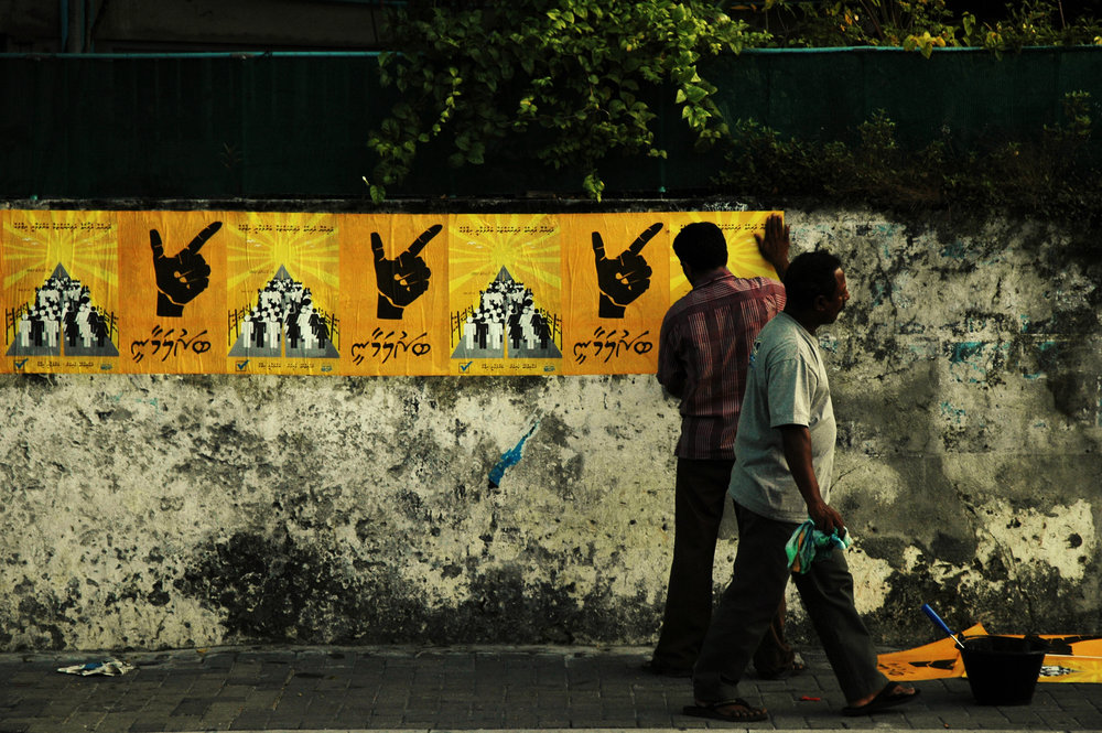 Man puts up MDP (Maldivian Democratic Party) poster advocating for the Barulamaanee (Parliamentary) System.  Male' City.  Nikon D70s.  (2007)