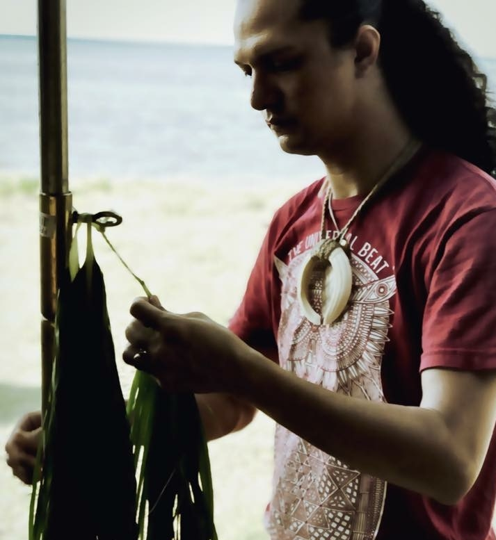 Kumu Paʻa Kawika Foster showing the students how to make lei (garland) of ti leaves