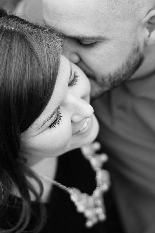 guy kissing girl on cheek engagement photo