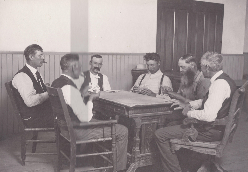 A game of pitch in the courthouse at Santa Fe, Kansas.  From L-R,  V.L. Bethel - county official, F.E. Murphy - county treasurer, James Patrick - Abstractor, Henry Johnson - county commissioner, George Wallace - probate judge and Mr. Ballentine.