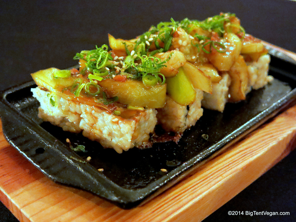 Garlic Eggplant Roll: Fried Tempeh and Avocado Roll topped with lightly sautéed Eggplant and a Garlic Miso Soy Sauce...served sizzling on a hot stone plate!
