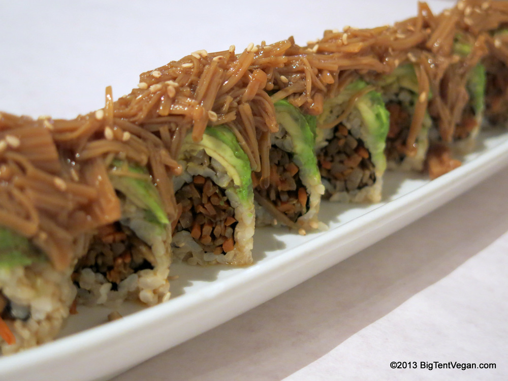Landscape of Japan: Braised Carrot and Burdock Root (Gobo) Roll, encased in thinly sliced Avocado and topped with an Enoki Mushroom Sauce .