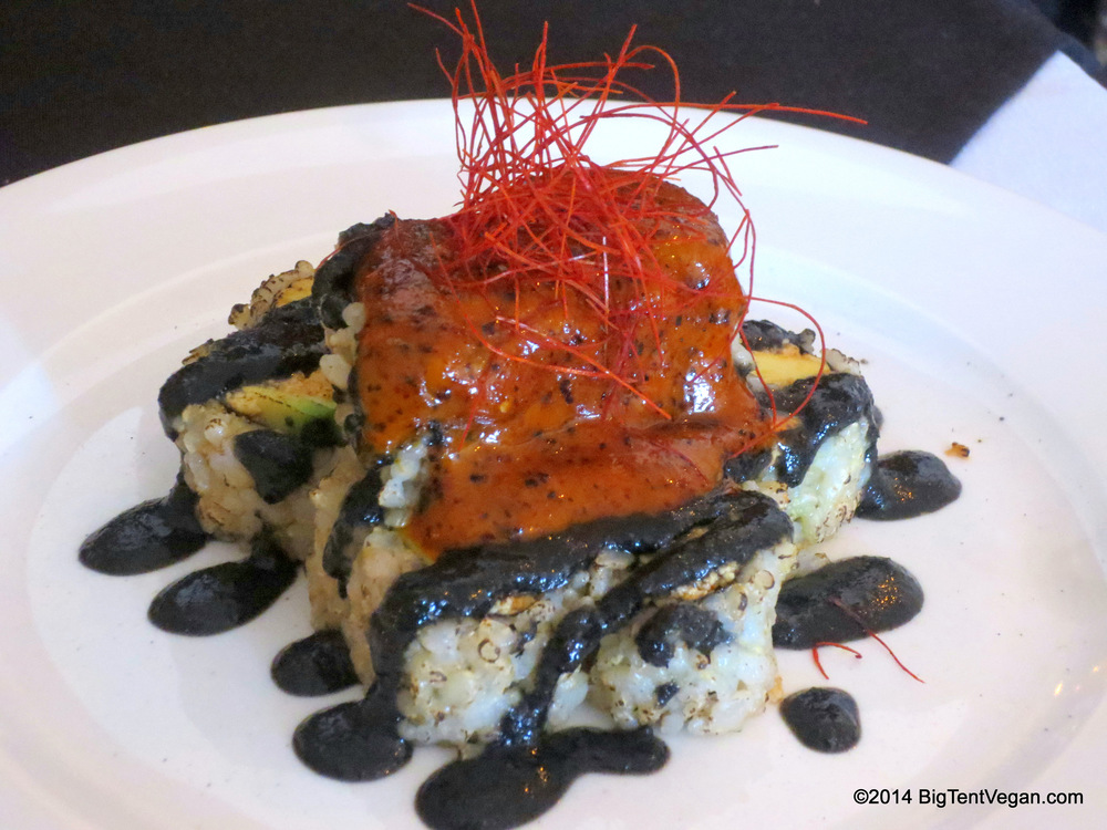 "Black Volcano: Spicy ""Tuna"" (tofu) and Avocado Roll, topped with house-made Black Sesame Tahini Sauce and Spicy Chili Mayo, garnished with delicate threads of Cayenne Pepper."