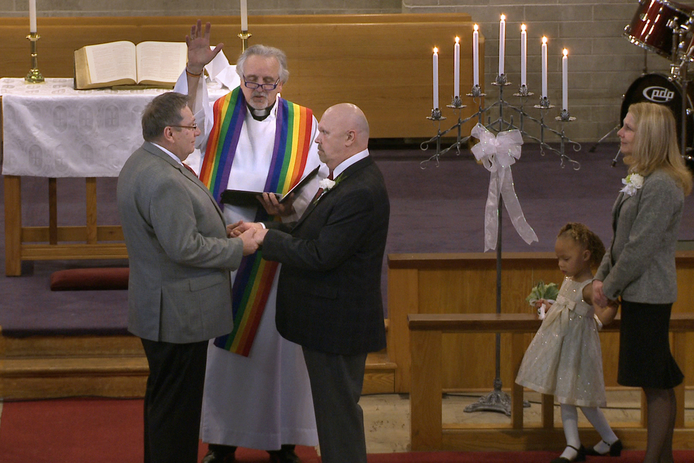 The Rev. Gordon Hutchins marries Wayne and Michael Simonson in their church, in defiance of current United Methodist Church law.