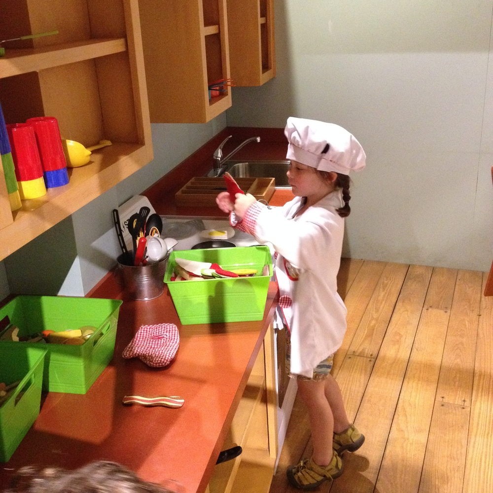 Théa playing chef at the Bayou Children's Museum. She also played doctor, construction worker, knight, fireman, railway conductor, and Batman that day at the museum.