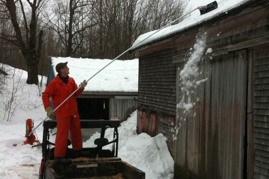 STEPHEN FREEMAN, WITH A LONG-HANDLED SCRAPER, ASSISTS COREY RHODENIZER, OWNER OF E-I-E-I-O FARM IN BLOCKHOUSE, N.S., IN CLEARING SNOW FROM A BARN NEAR ONE THAT COLLAPSED UNDER WET SNOW SATURDAY NIGHT.