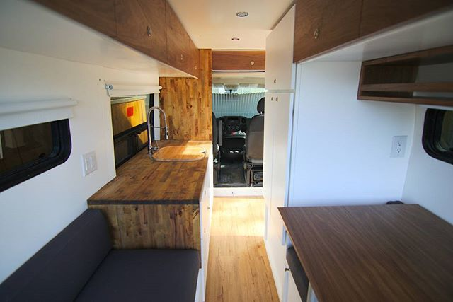 "136"" ProMaster High Roof with large sink and drop down sprayer faucet. Swivel table removable in the dinette space when you convert to bed at night.  #rossmonstervans #customvans #customcabinetry #crlaurence #motionwindows"