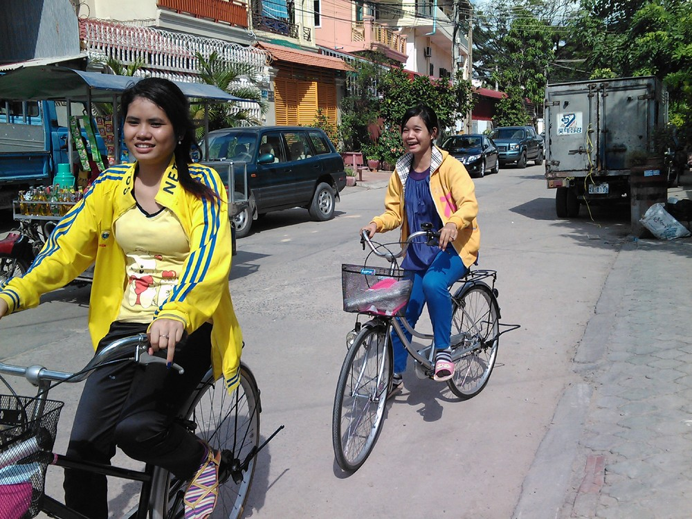 Mealea, left, and friend ride through Banteay Meanchey