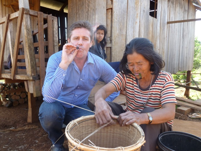 Mr. Glenn pretending to smoke local tobacco alongside a weaver in Mondulkiri Province, Cambodia
