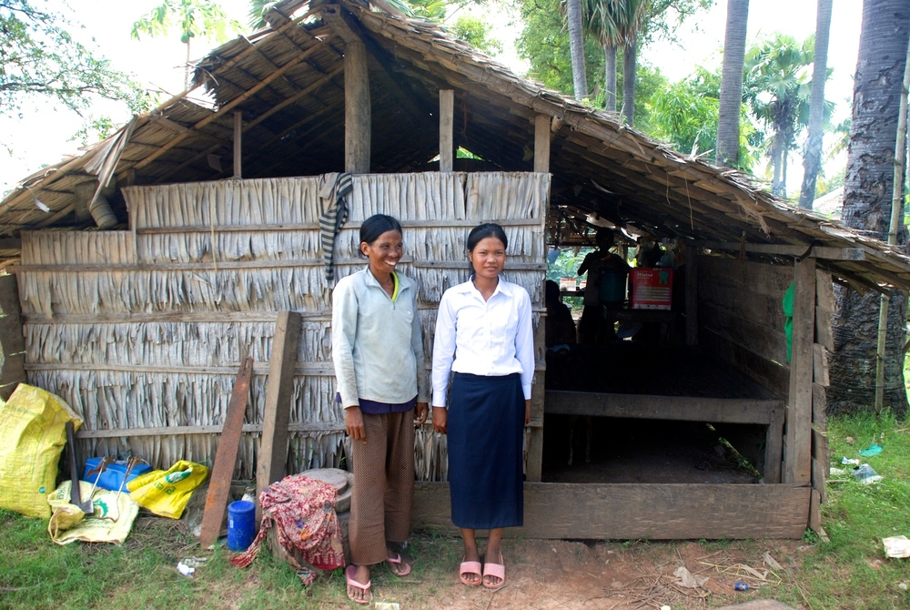 Suen Sokpoan stands in front of her home with her mother Dep Roan