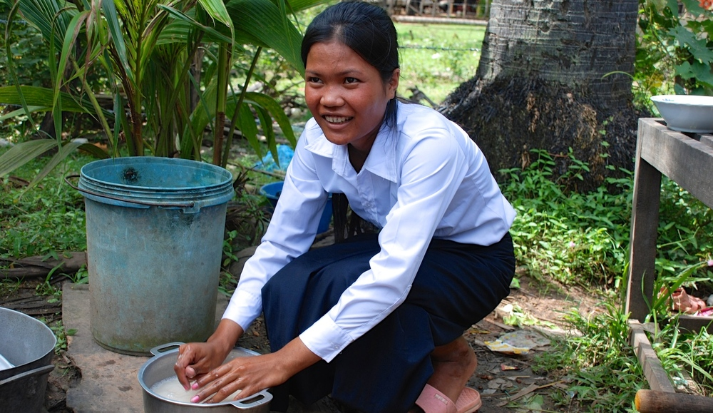 Sokpoan smiling brightly while prepares rice for lunch