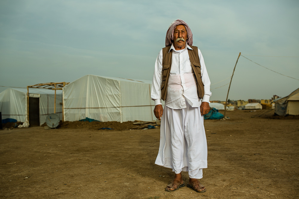 """Everyone takes photos of me. Thank God my face is great.""    Khuder, 71, escaped with his family, including 24 grandchildren, in August 2014 when Daesh invaded Sinjar mountain. They now live in makeshift tents outside of Khanke refugee camp in northern Iraq. There are approximately 20,000 people inside the camp and another 20,000 - 30,000 people living outside the camp."
