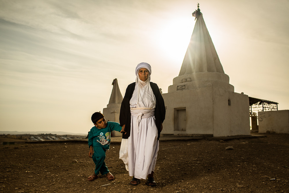 """Everyday I come here and I ask God if anyone can help us.""    Adul, 60, stands with her deaf and mute granddaughter Rajja, 14, in front of the Baba Chawish Yazidi temple outside of the Khanke refugee camp."