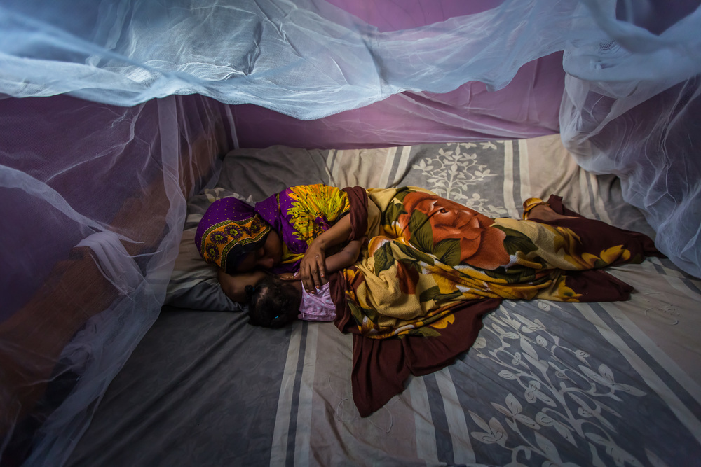 Habiba Suleiman, 28, a District Malaria Surveillance Officer (DMSO) lies under a bed net with her daughter at their home in Zanzibar, Tanzania.