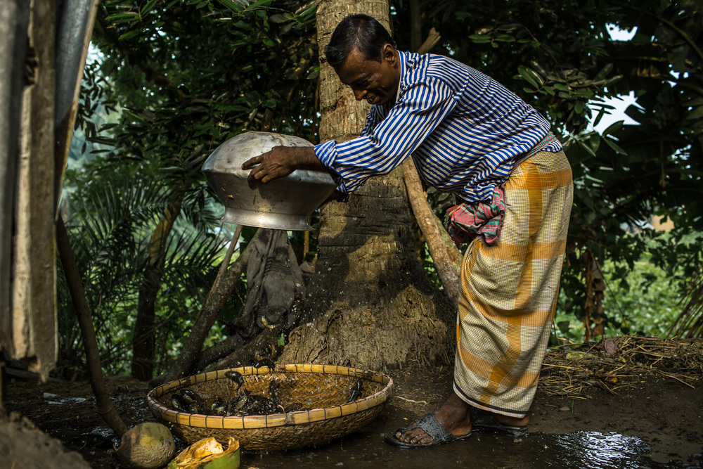 Taroni and his wife harvest fish from a nearby pond to prepare for breakfast.
