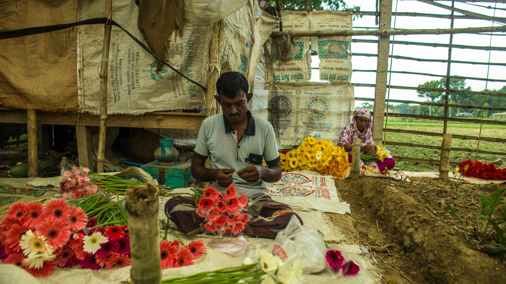 Through training, Sajeda learned how to better package her flowers and connect to buyers. Her husband, Imamul Hossain, helps her package flowers before they are taken to the market. Photo by Josh Estey