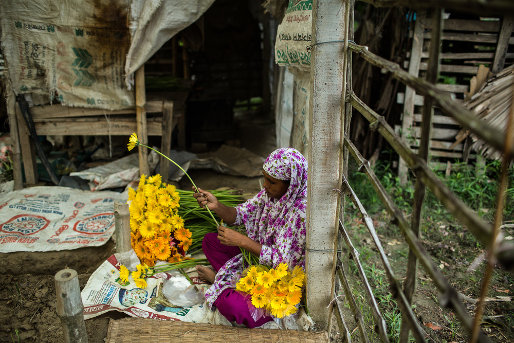 Sajeda packages her flowers with plastic to help protect them before selling them. Photo by Morgana Wingard