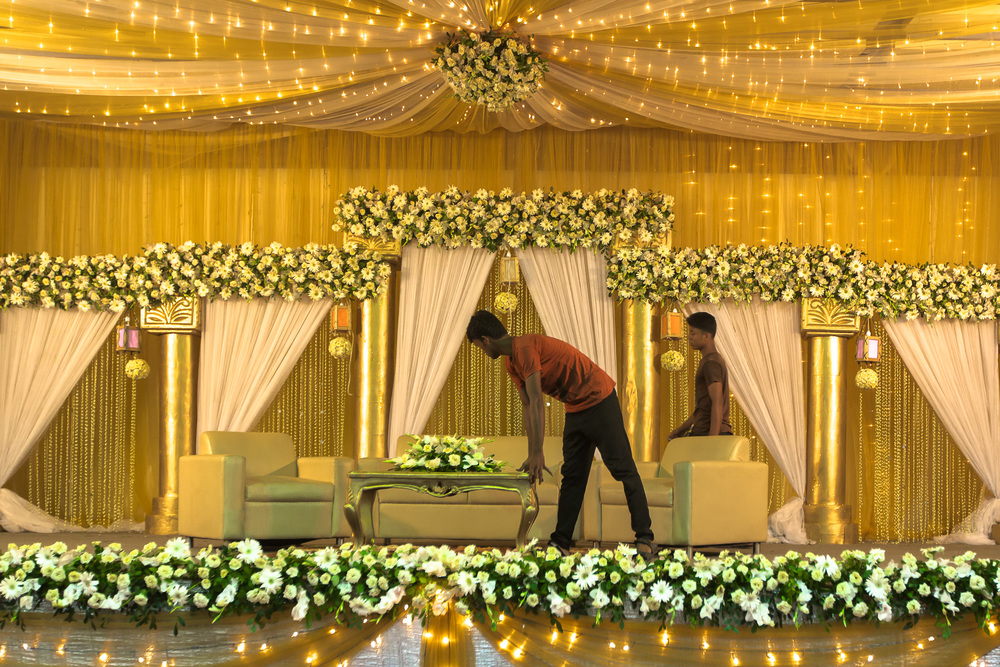 Wedding coordinators prepare a venue with flowers grown in Bangladesh for an evening wedding. Photo by Morgana Wingard
