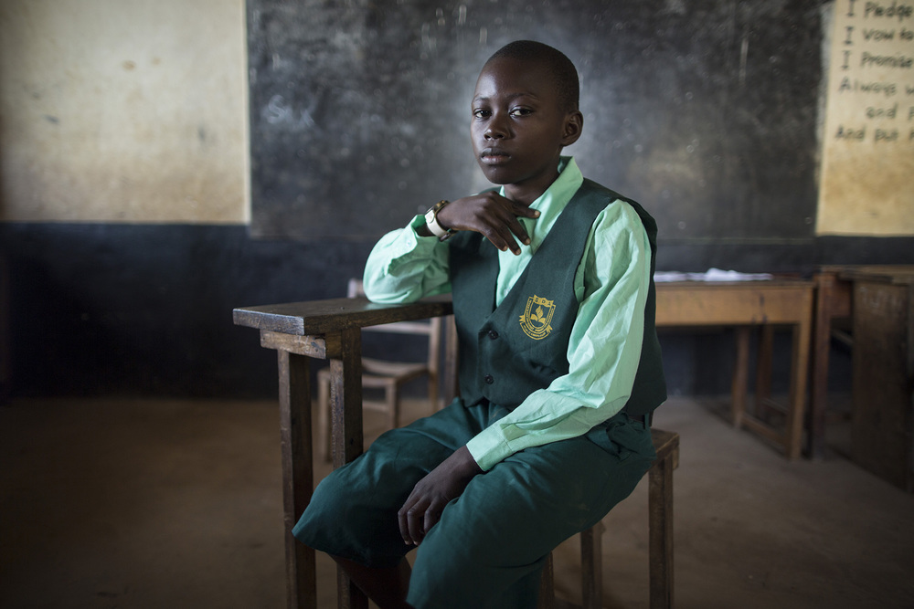 "WATERLOO, SIERRA LEONE: When Ebola came into the country, the school that Jan Sankoh, 13, attended was suspended. ""I sat lonely at home. I was scared so I stayed in the house,"" he remembers. He started talking to his neighbors about taking proper precautions like washing their hands.  He says, ""I told my neighbors that you should wash your hands even when Ebola is not here."" They said it was good and to go to them every day to talk about Ebola. His father was working for an NGO to provide rice for Ebola patients at the ETU. His mother stayed at home with and his younger brother ands sister. She made sure they were always using precautions. He says, ""Not all people believe in Ebola. Some people say it's the government making people sick. "" He would tell people who believed that way, ""you should believe that Ebola is real."" Instead of thinking people have Ebola around him, he'll wear protective clothes so he keeps from judging people. ""I want Sierra Leone to be a good country. I want us to stop judging people, stop corruption, stop teachers asking for money for grades, and bad guys doing stuff to girls like rape. Children have the right to go to school every day. When you learn, you will have everything."" Jan is now in the 6th grade. He says, ""I want to be a scientist. I want to study about the stars and the moon. At night, they are lighting, moving – the last time at my house I saw a star running. That's why I want to be a scientist."" Photo by Sarah Grile"