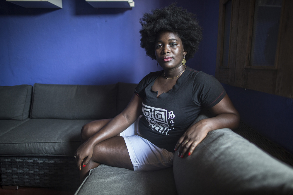 "MONROVIA, LIBERIA: Pandora Hodge was an entrepreneur and student studying Public Administration and Sociology before the Ebola outbreak in Liberia. She had been renovating her restaurant for about a year and a half and working with Kriterian Monrvovia—an independent arthouse cinema. When Ebola came into the country, everything stopped. Since Kriterian had already set up cinema showings in communities, she felt they could take advantage of the opportunity and start talking to people about the disease. 72 students got involved and started going out door-to-door. The Ministry of Health trained the volunteers and UNICEF supplied them with flyers. They reached 400 communities between Aug. 2013 and the beginning of 2015. Before going out into the communities, they would always inform the leaders. Once on location, they would start by talking to people who were willing to listen to their message. During the height of Ebola in Liberia, she realized there was not enough focus outside of Monrovia. They reached out to the President's office and were given 2 video cameras and one still camera to document everyday activities. These clips would later be edited into a documentary. She recently opened up her restaurant in Monrovia and is now working on renovating an old theatre in downtown to create the cinema house. Pandora says she hopes to, ""impact many Liberians to be able to work hard, to put all their dreams for Liberia and to bring it to reality. That's when we know these wishes that we have are going to work. I was born into the war in Liberia. From the first time I had the freedom to do what I wanted, I used it for the best."" Photo by Sarah Grile"