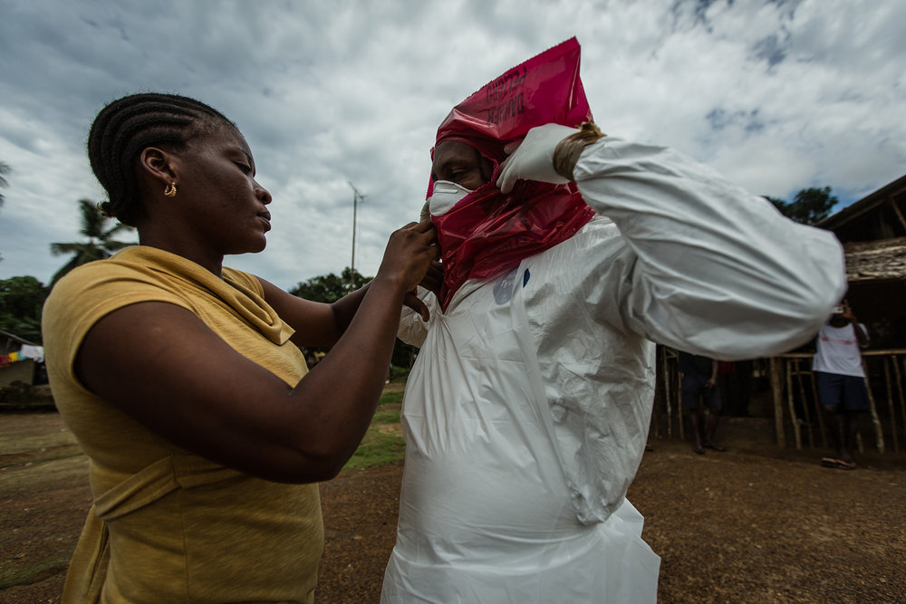 Varbah helps seal Melvin's Personal Protective Equipment (PPE) as he suits up to remove the body of Phelica Anthon, 6, in Arthingon, Liberia.